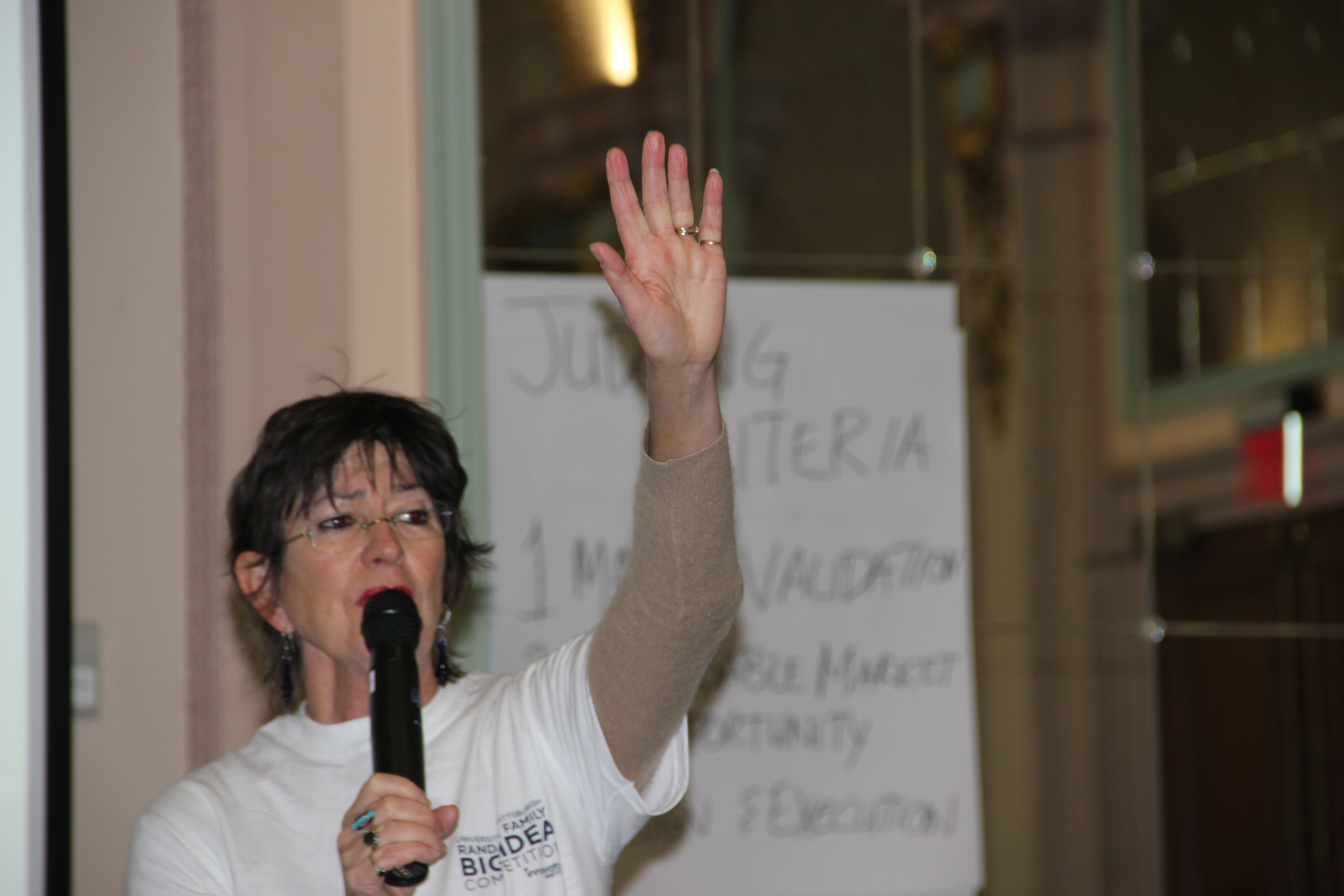 Babs Carryer speaking into mic with one hand up in the air