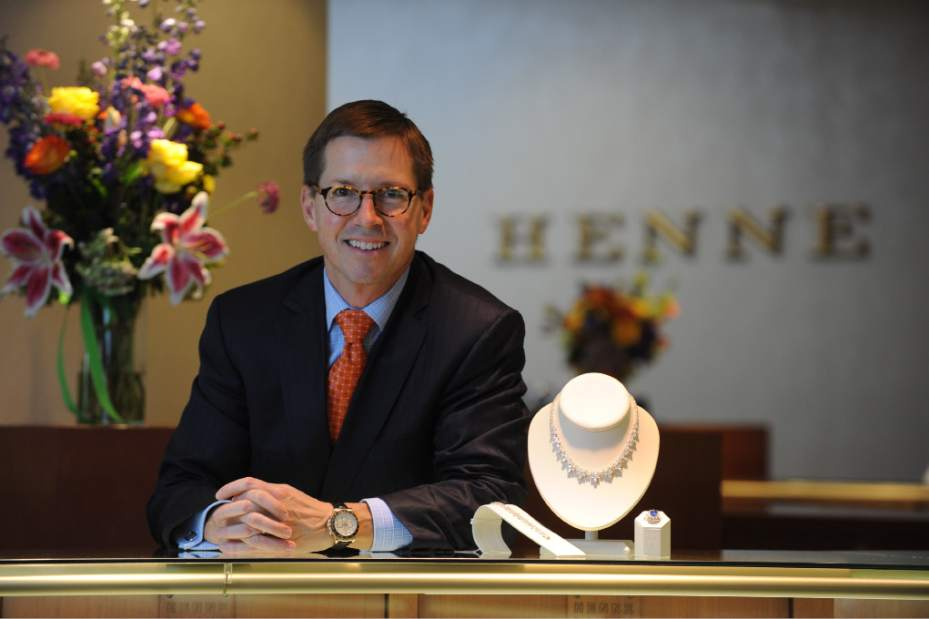 John Henne smiling at counter with a beautiful diamond necklace, ring, and earrings displayed to the right of him