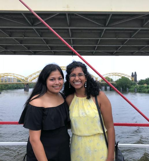 Eva Roy and Anjana Murali smiling in front of Pittsburgh skyline